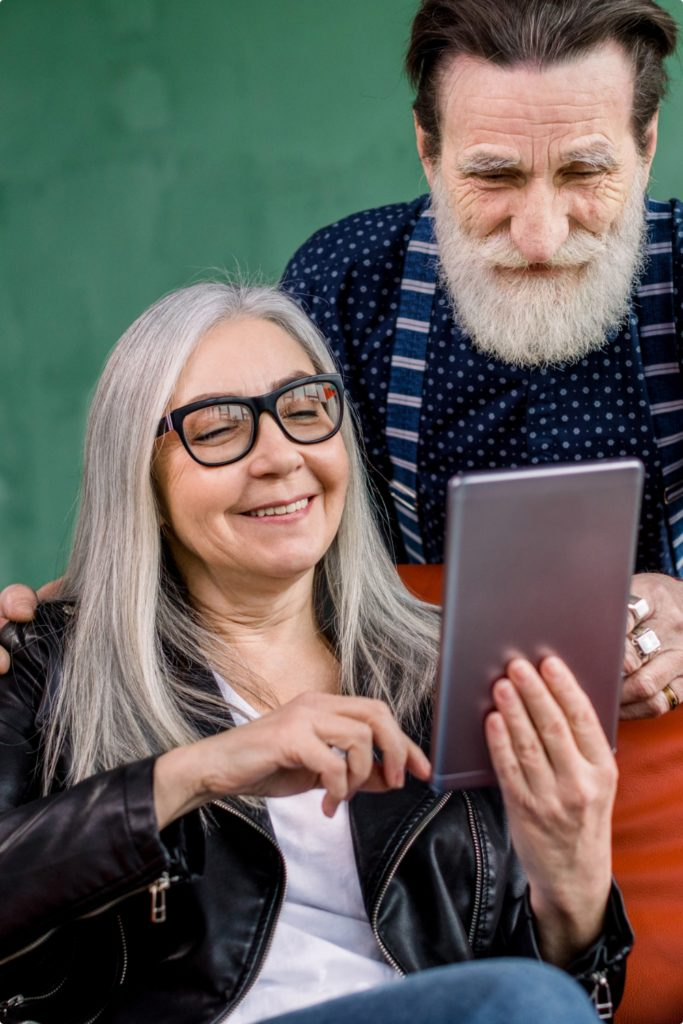 portrait-smiling-attractive-senior-couple-bearded-man-gray-haired-woman-using-digital-tablet-spending-time-together-browsing-internet-social-networks